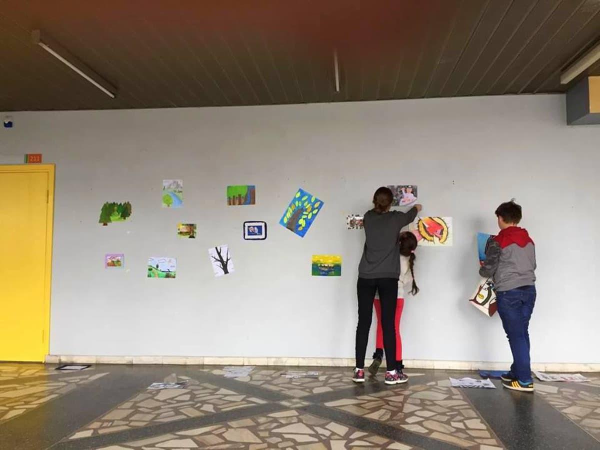 Mokiniai mokosi eksponuoti piešinius, sukurti parodos sieną.