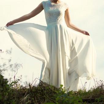 Trijų dalių suknelė. Bodis, labai tankiai puoštas rankų darbo nėriniais. Prie bodžio siūti trumpas ir ilgas saulės kliošo sijonai paraukti ties liemeniu.