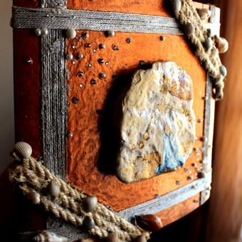 Akmuo, medis, virvės ir jūros kriauklių mišinys papuošiantis jūsų namų sieną.