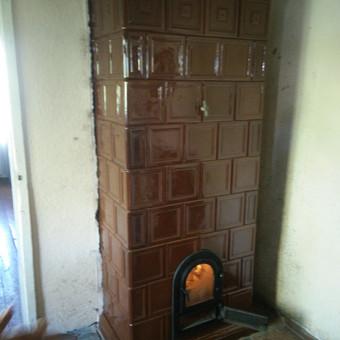 Rudų, glazūruotų koklių šildymo krosnis. Atrestauruota (išardyta ir naujai perstatyta)