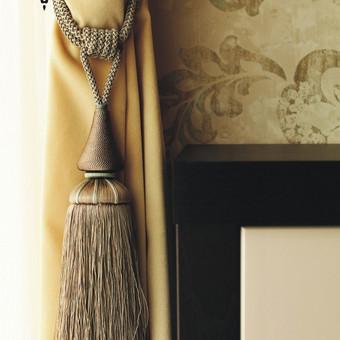 Naktinės užuolaidos audynys parinktas lovos galvūgalio spalvos, o parišimo kutas dekoruotas žalsva virvele, kurios spalva atsikartoja tapetuotoje sienoje.