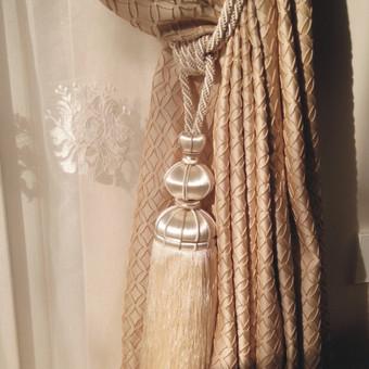 Dieniniame audynyje esantis ornamentai dekoruoti minimalia virvele, kuri atsiranda ir parišimo kute, naktinėje užuolaidoje. Kuto forma tarsi atkartoja centrinio šviestuvo detales. O atsiradusi pilka spalva susišaukia su minkštų baldų gobelenu, kilimu.