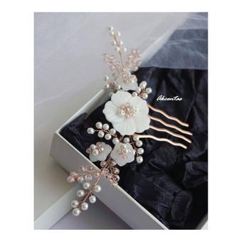 Romantiškas akcentas. Rausvo aukso detalės plaukuose dera su tradicinio rausvo aukso žiedais.