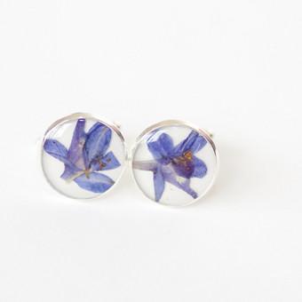 Į ausį veriami auskarai su tikru gėlės žiedu.