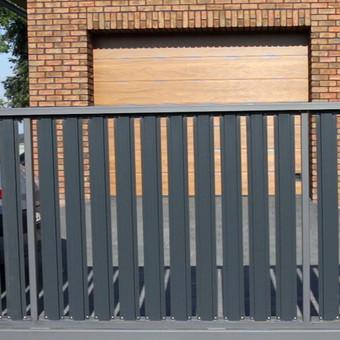 Ilgaamžiai ir kokybiški stumdomi vartai su vertikalių tvoralenčių užpildu.