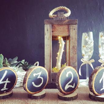 Stalo dekoracijos: stalo numeriai, žibintai, dekoruotos taurės